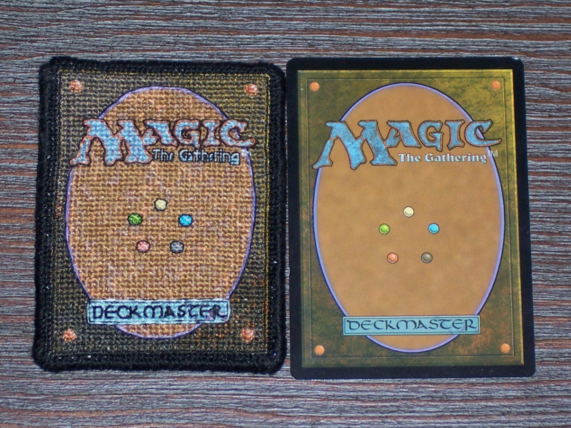 A side-by-side comparison of the back side of the stitch project and the back of an actual MtG card; the two are very nearly the same size (the stitchpiece being ever-so-slightly smaller).