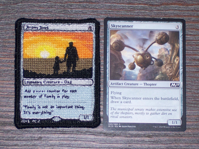 A side-by-side comparison of the front side of the stitch project and an actual MtG card (Skyscanner).  Instead of being a copy of an existing card, the stitched card is personalized for the recipient.